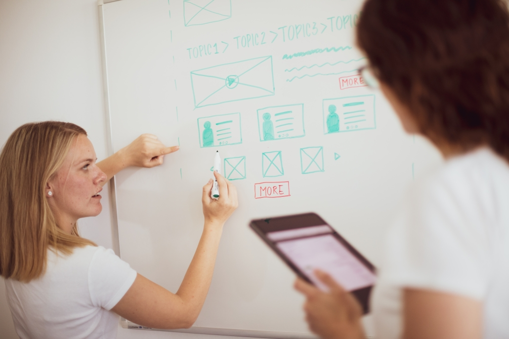 woman draws wireframes on whiteboard